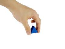 手拿着在白色背景的一个蓝色三角 免版税库存照片