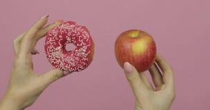 手拿着多福饼和苹果 反对苹果的挑选多福饼 r 股票视频