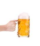 手拿着大杯子用金啤酒。 免版税库存图片
