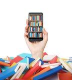 手拿着有一个书架的一个智能手机在屏幕上 五颜六色的书堆  教育和技术的概念 isola 免版税库存图片
