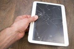 手拿着有残破的触摸屏幕的片剂个人计算机 库存图片