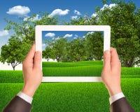 手拿着有自然风景的片剂个人计算机  库存照片