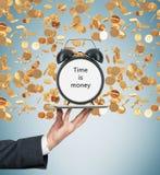 手拿着有闹钟的一种片剂 金黄硬币从天花板跌倒 时间的概念是金钱 库存照片