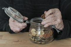 手拿着有零钱的一个金属螺盖玻璃瓶 图库摄影