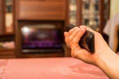 手拿着电视遥控 免版税库存照片