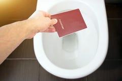 手持在洗手间的公民` s护照,把他的护照扔出去 概念-公民身份,护照,波尔布特损失的变动  免版税库存图片
