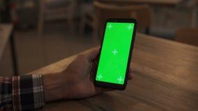 手持绿色模拟屏智能手机的特写 使用应用 现代手机 背景中的舒适 影视素材