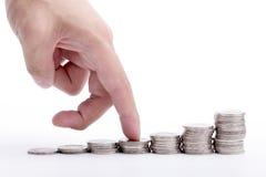 手指上升至栈顶硬币 免版税图库摄影