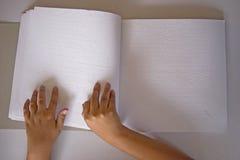 手指和盲人识字系统。 盲人人员读了在盲人识字系统的一本书。 免版税库存照片