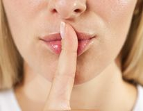手指嘴唇shh妇女 库存照片