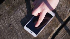 手指姿态女孩处理在木背景的智能手机 股票录像