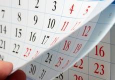 手指拿着日历板料 免版税库存照片