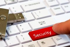 手指新闻一个红色按钮以在一个白色键盘的文本安全有USB闪光驱动的 库存照片