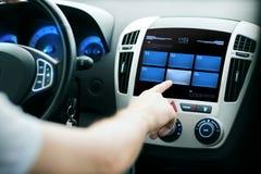 手按在汽车控制板屏幕上的按钮 免版税库存图片