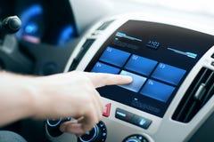 手按在汽车控制板屏幕上的按钮 库存图片