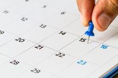 手按在第15的别针在日历的月 免版税库存图片