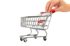 手按有圣诞节花、一品红和一个装饰球的小购物车 库存图片