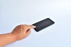 手接触在白色背景的黑色智能手机 免版税库存图片