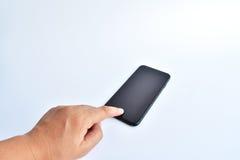 手接触在白色背景的黑色智能手机 库存图片
