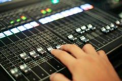 手推挤有音量控制器和a的一个专业音频混合的控制台 库存图片