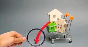 手推车和下来箭头的木房子 减少的兴趣在抵押上 在物产价格和公寓的一种衰落 免版税图库摄影