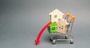 手推车和下来箭头的木房子 减少的兴趣在抵押上 在物产价格和公寓的一种衰落 库存照片