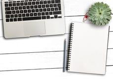 手提电脑、空白的笔记薄和铅笔和多汁植物在土气白色木书桌上 库存图片