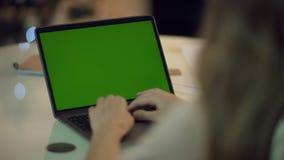 手提电脑妇女手键入的键盘有绿色屏幕的在家 影视素材