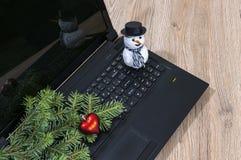 手提电脑,圣诞树分支和一个雪人在木 免版税库存照片