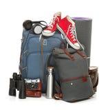 手提箱、运动鞋、减速火箭的照相机、karrimat和双筒望远镜在白色背景 免版税库存图片