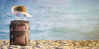 手提箱和帽子在海滩 免版税库存图片