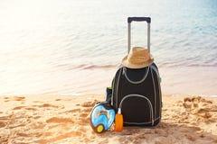 手提箱和帽子,与面具的遮光剂 热带海,海滩在背景中 夏天休闲的概念 免版税库存照片