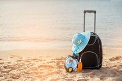 手提箱和帽子,与面具的遮光剂 热带海,海滩在背景中 夏天休闲的概念 库存图片