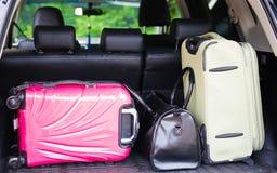 手提箱和袋子在准备好汽车的后车箱离去在假日 库存图片