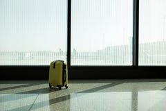 手提箱在机场离开休息室,飞机在背景,暑假概念,旅客手提箱中在机场 免版税库存图片