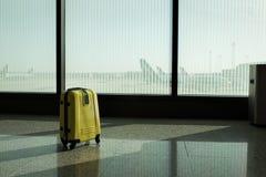 手提箱在机场离开休息室,飞机在背景,暑假概念,旅客手提箱中在机场 免版税库存照片