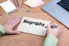 手文字传记 有膝上型计算机和文具的办公桌 免版税库存图片