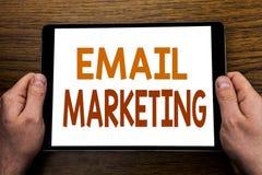 手文字文本说明电子邮件营销 在片剂膝上型计算机写的网上网促进的企业概念,木背景w 免版税库存照片
