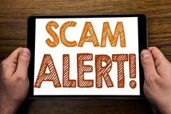 手文字文本说明诈欺戒备 在片剂膝上型计算机写的欺骗警告的企业概念,与事务的木背景 免版税库存图片