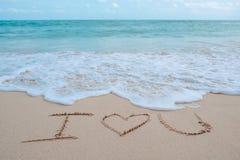 手文字词我爱你在海的海滩有白色波浪和蓝天的 库存照片