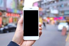 手智能手机的藏品嘲笑有城市街道背景 免版税图库摄影