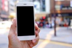 手智能手机的藏品嘲笑有城市街道背景 免版税库存图片