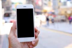 手智能手机的藏品嘲笑有城市街道背景 库存照片