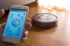 手有应用控制机器人吸尘器的藏品智能手机 免版税库存图片