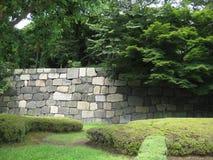 手有树和草坪的被放置的石墙 免版税库存图片