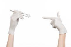 手术和医学题材:在拿着有拖把的一副白色手套的医生的手外科钳位隔绝在白色背景 免版税图库摄影
