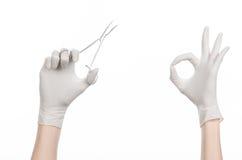 手术和医疗题材:在拿着一个外科夹子的一副白色手套的医生的手被隔绝在白色背景 免版税库存照片