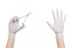 手术和医疗题材:在拿着一个外科夹子的一副白色手套的医生的手被隔绝在白色背景 库存照片