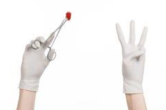 手术和医疗题材:在拿着有血淋淋的棉塞的一副白色手套的医生的手一个外科夹子被隔绝 免版税库存照片