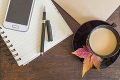 手机、咖啡与秋叶,笔记本和工艺纸在木甲板 图库摄影